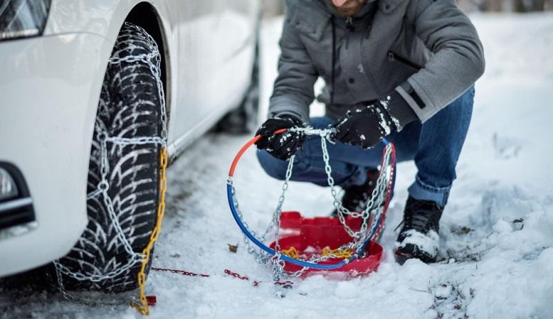 بستن زنجیر چرخ روی تایر خودرو در هوای برفی زمستان